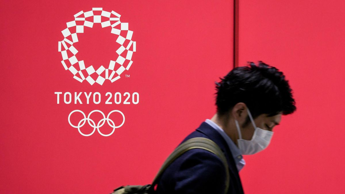 A man in a face mask walks past the Tokyo 2020 logo