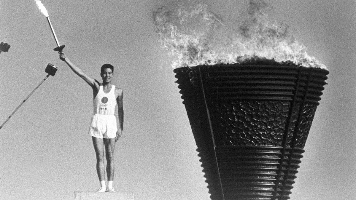 Yoshinori Sakai, the final runner in the torch relay, lights the Olympic cauldron during the opening ceremony of the Tokyo Olympics on Oct. 10, 1964.