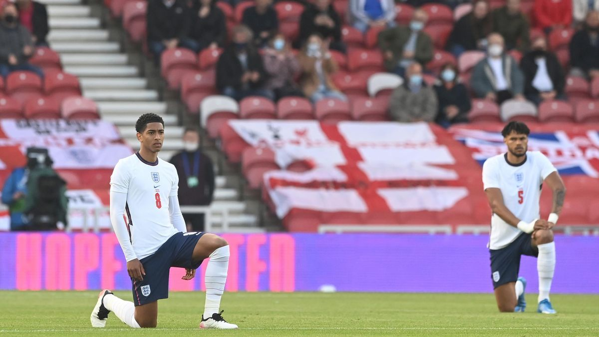 Jude Bellingham and Tyrone Mings of England take the knee ahead of the international friendly match between England and Austria