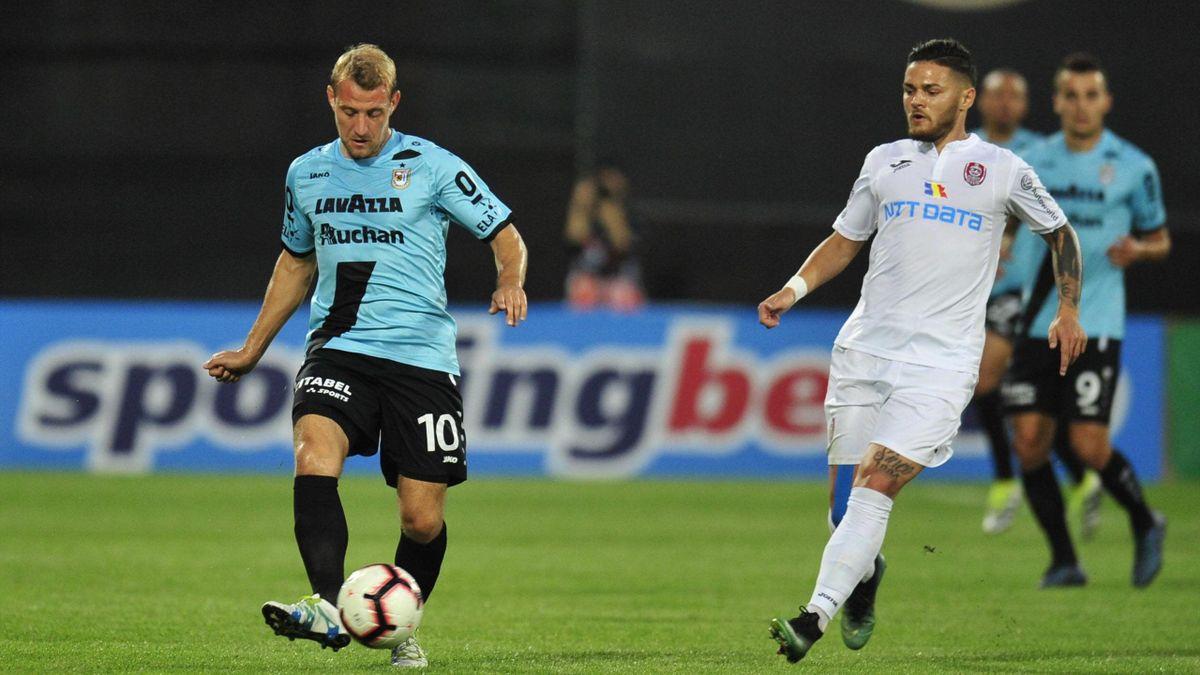 F91 Dudelange-CFR Cluj, preliminari Europa League 2018-2019: Dominik Stolz (Dudelange, maglia azzurra) porta palla tallonato da Alexandru Ionita (CFR Cluj, maglia bianca) (Imago)
