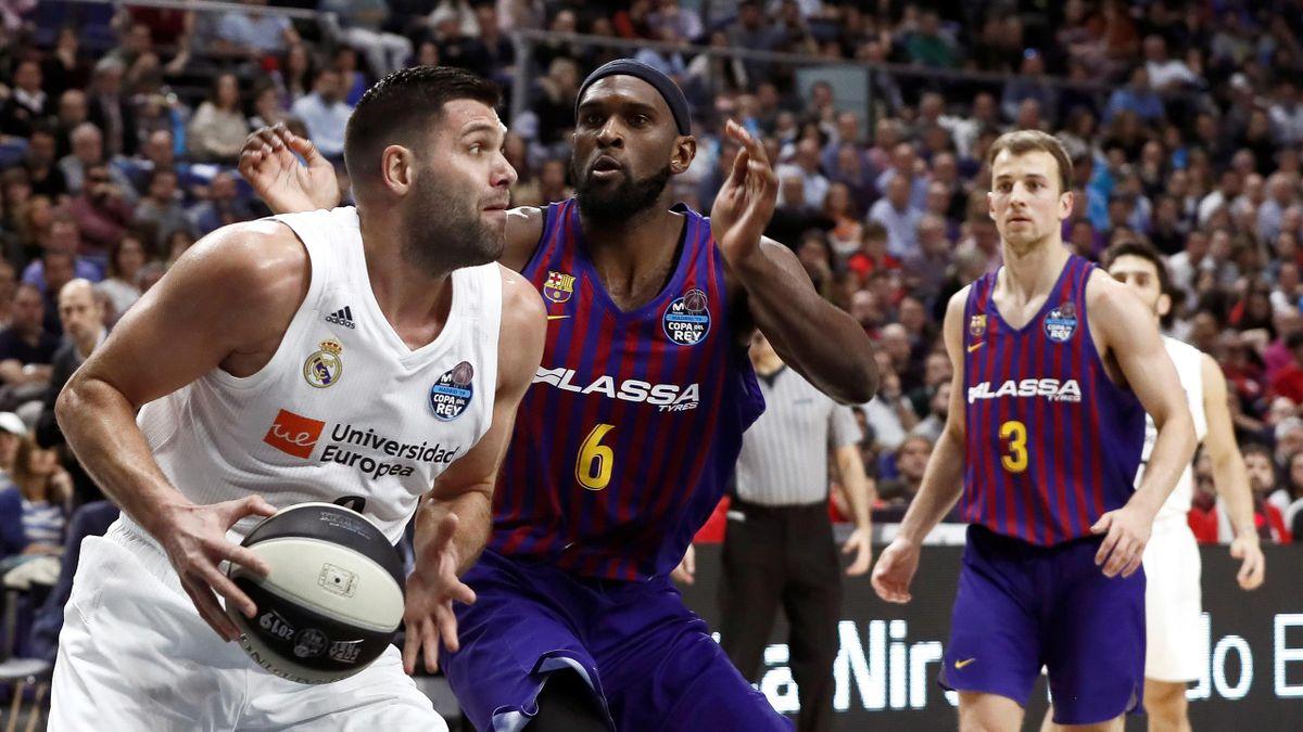El jugador del Real Madrid Felipe Reyes (i) juega una pelota ante Chris Singleton (c), del Barcelona Lassa, durante la final de la Copa del Rey de baloncesto