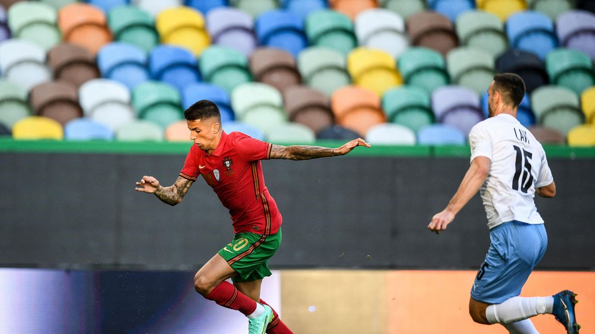 Portugal's defender Joao Cancelo (L) is challenged by Israel's midfielder Neta Lavi during the international friendly football match between Portugal and Israel at the Jose Alvalade stadium in Lisbon in preparation for the UEFA EURO 2020 football competit