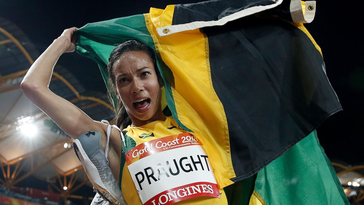 Aisha Praught holds her national flag after winning the athletics women's 3000m steeplechase final during the 2018 Gold Coast Commonwealth Games