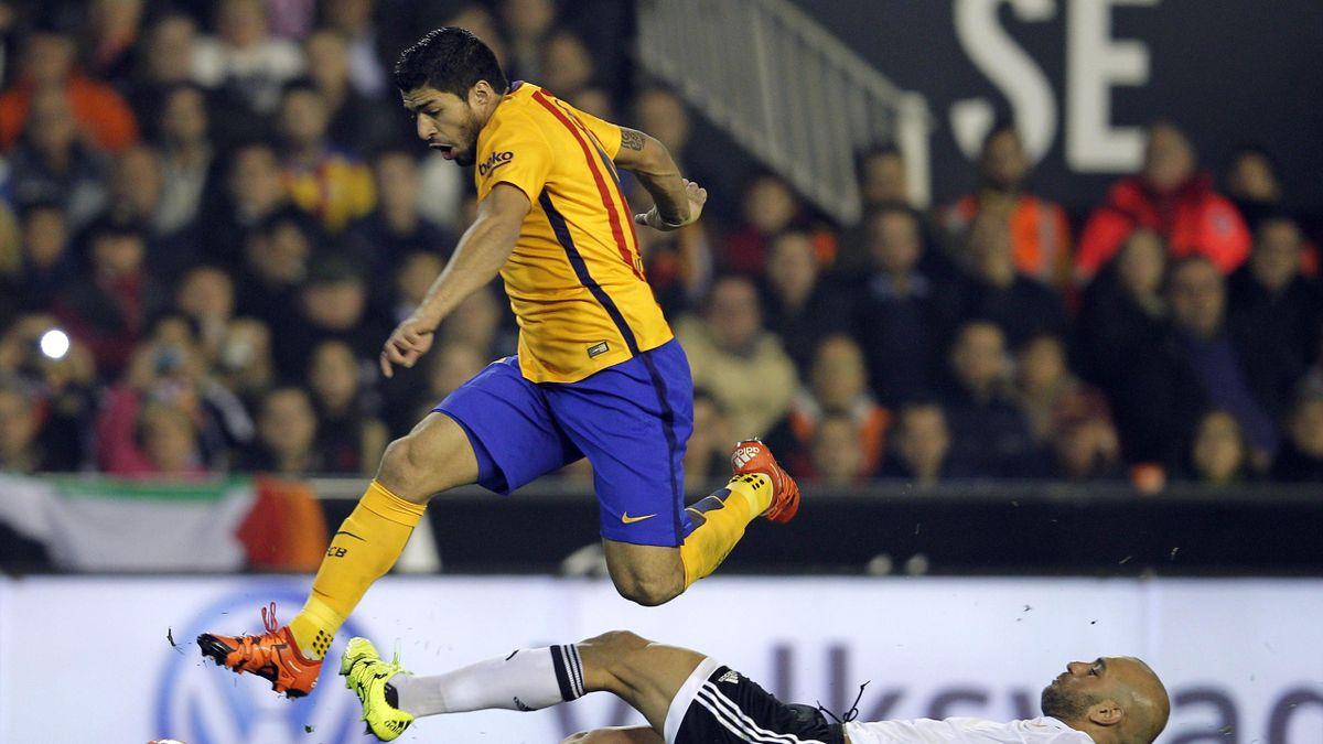 Barcelona's Uruguayan forward Luis Suarez (L) jumps over Valencia's Tunisian defender Aymen Abdennour