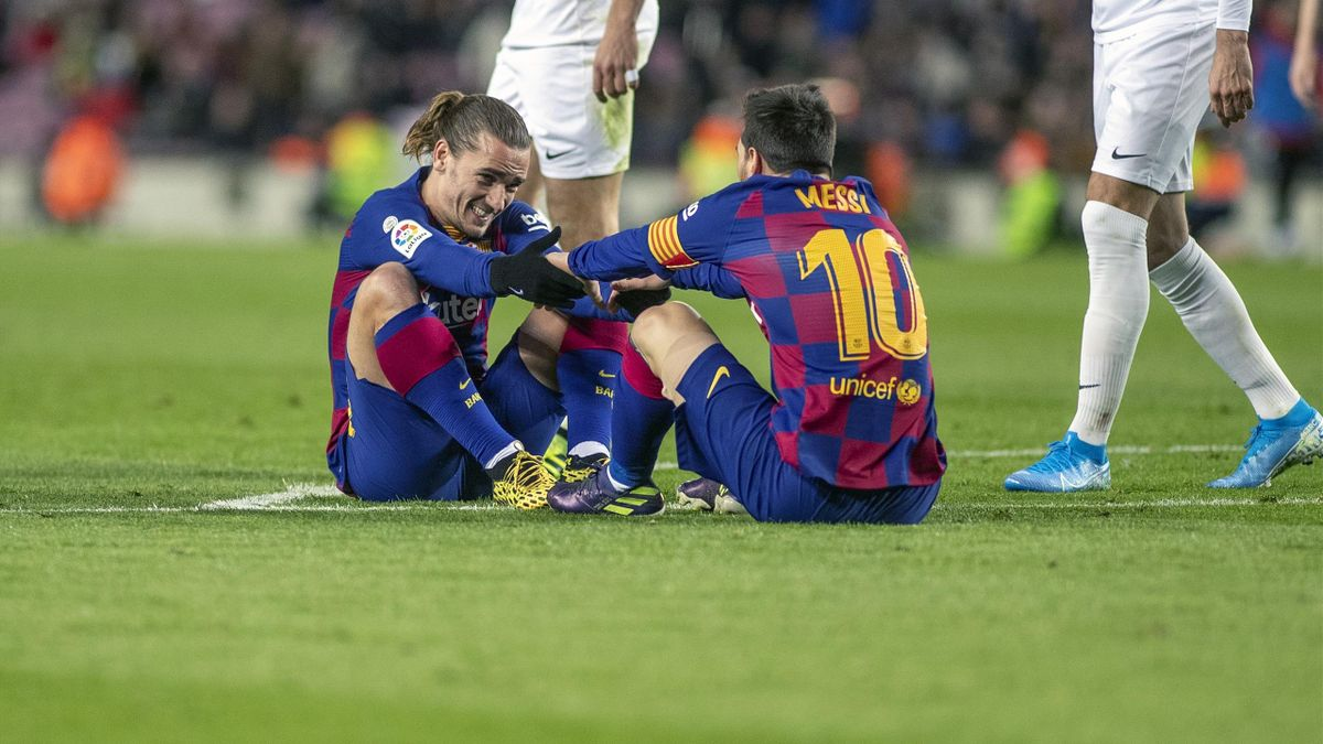 BARCELONA, SPAIN - January19: Antoine Griezmann #17 of Barcelona and Lionel Messi #10 of Barcelona pick each other up after both falling at the edge of the penalty area following foul during the Barcelona V Granada, La Liga regular season match at Estadio