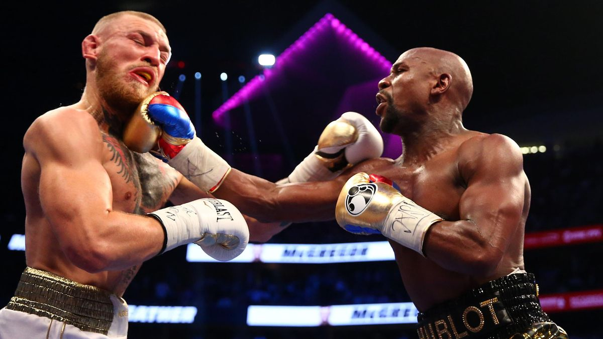 Mayweather Jr. lands a hit against Conor McGregor during a boxing match at T-Mobile Arena
