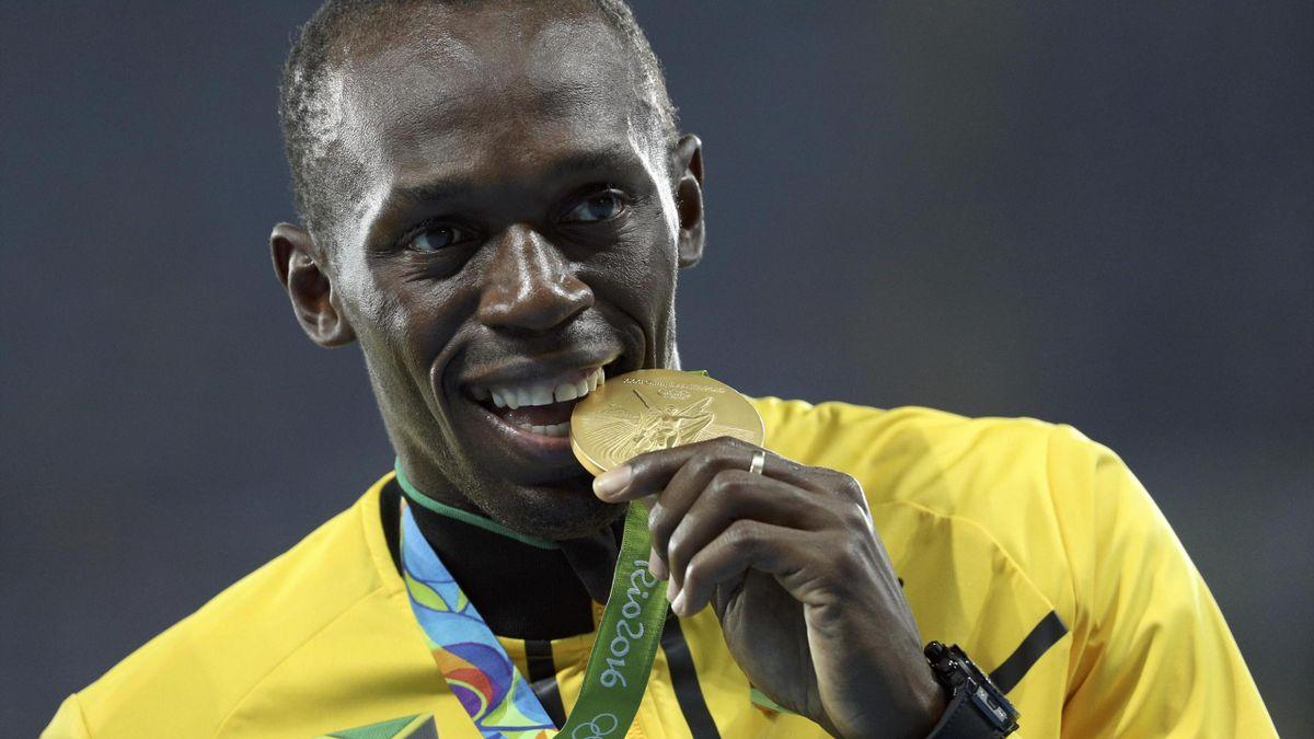 Gold medalist Usain Bolt (JAM) of Jamaica bites his medal.