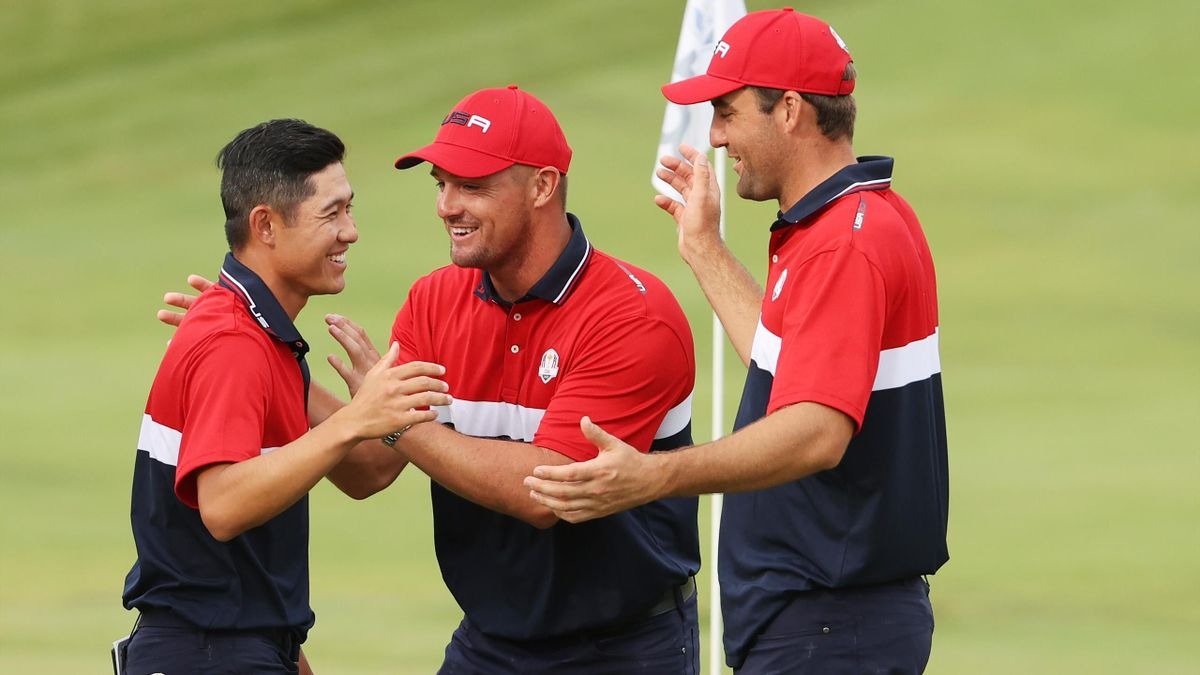 Collin Morikawa of team United States celebrates on the 18th green with Bryson DeChambeau of team United States and Scottie Scheffler of team United States after winning the half point needed to win during Sunday Singles Matches of the 43rd Ryder Cup.